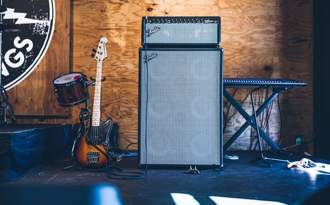grey and black PA speakers near electric guitar and drum