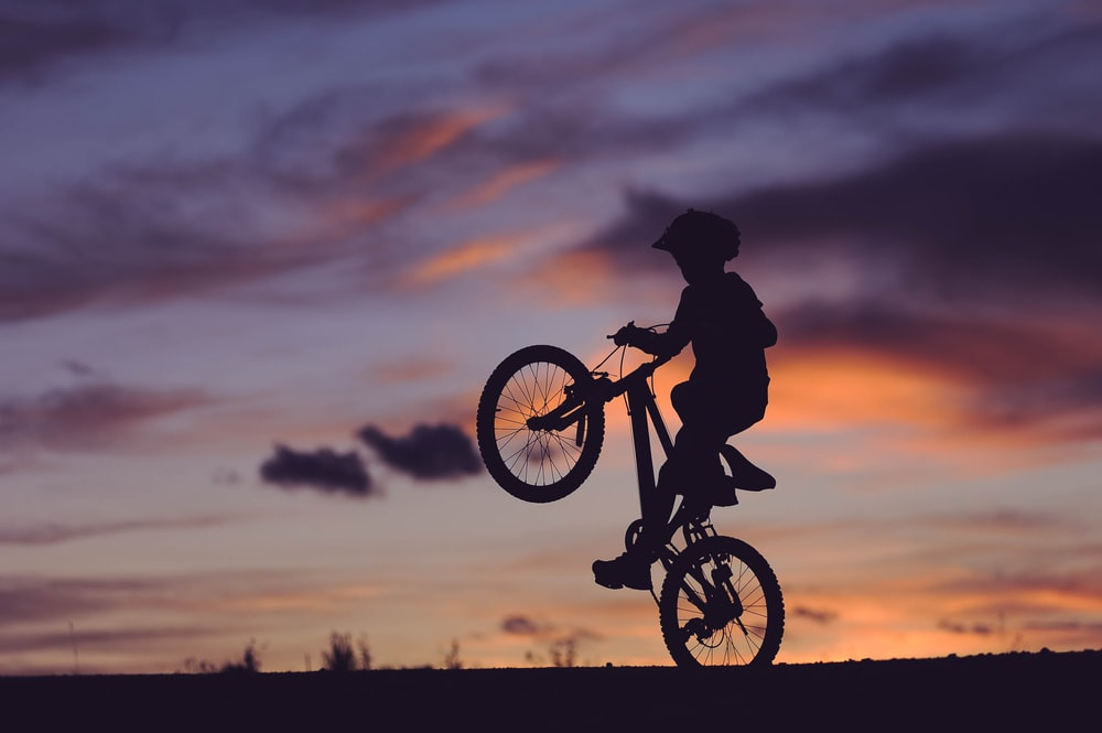 silhouette of boy riding bicycle in wheelie during golden hour