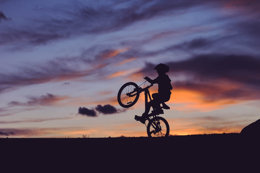 silhouette of child riding on bike