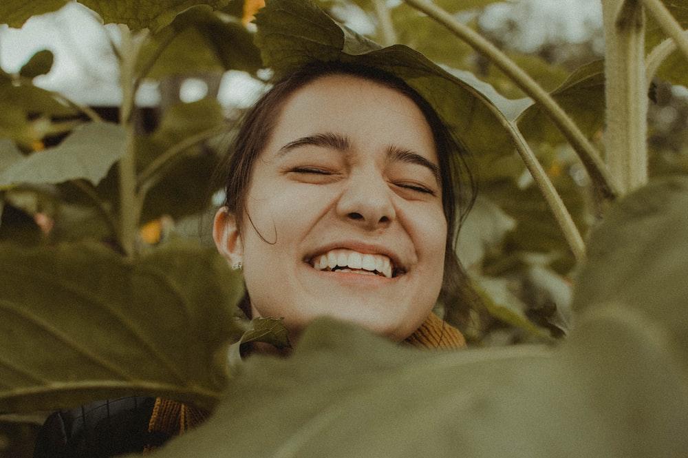 woman smiling between plants