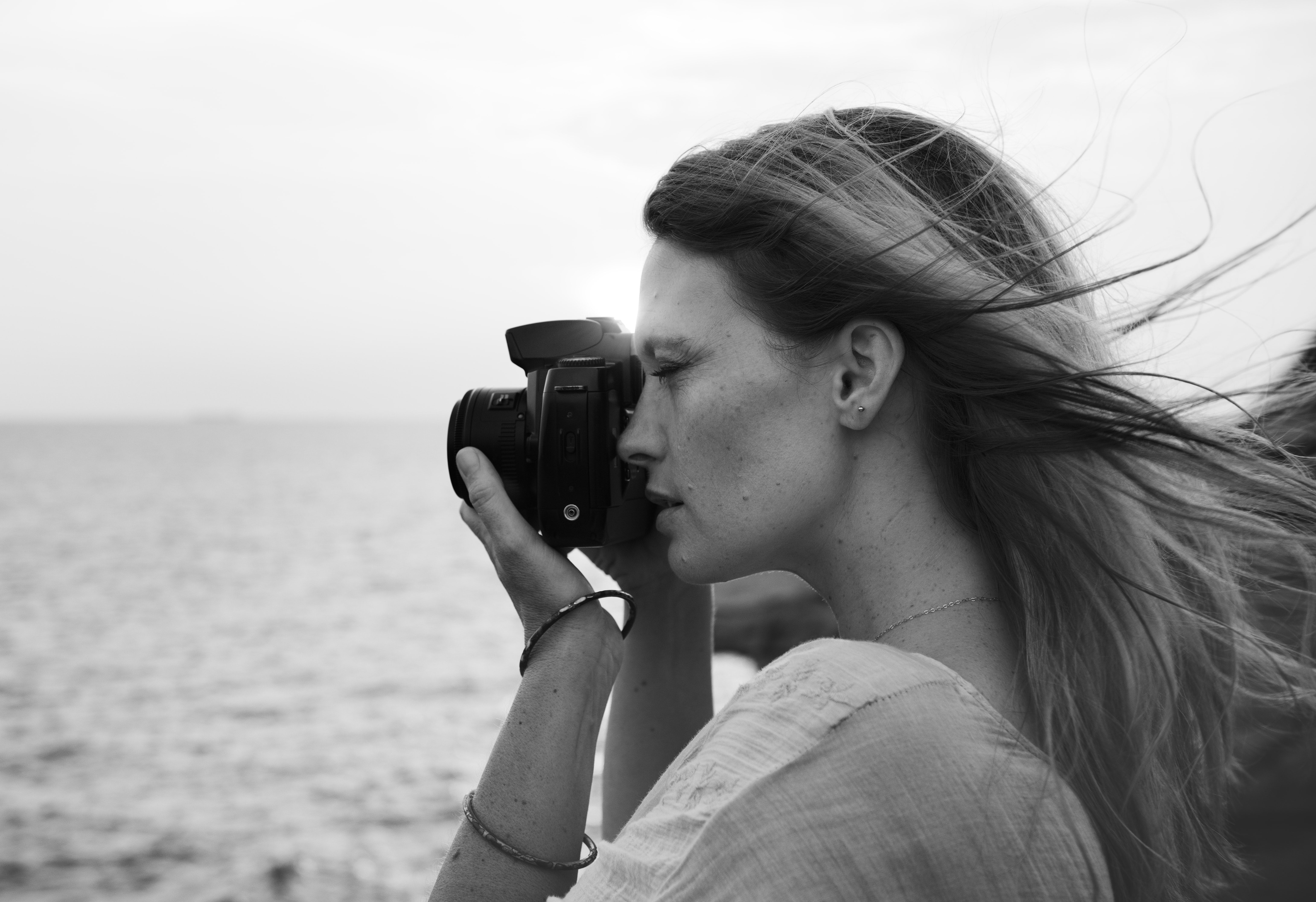 grayscale photo of woman taking photo using black DSLR camera