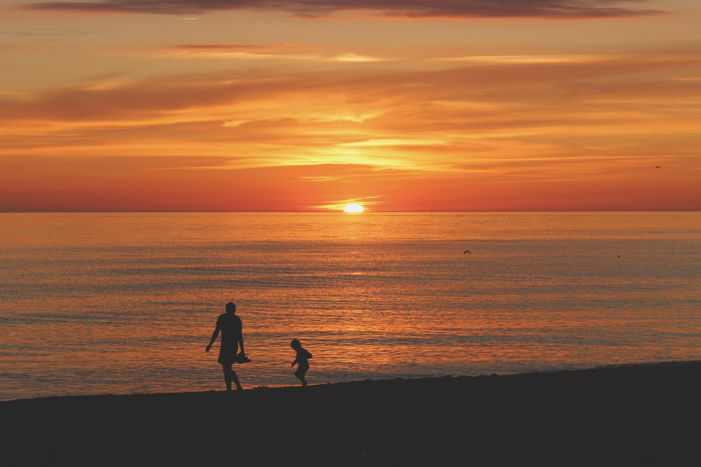 silhouette woman and chil on seashore