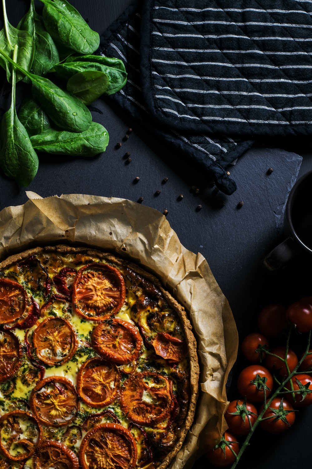 flat lay photography of two black pot holders beside tomatoes and pizza
