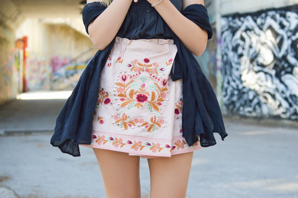 woman wearing black off-shoulder blouse and pink and multicolored floral skirt