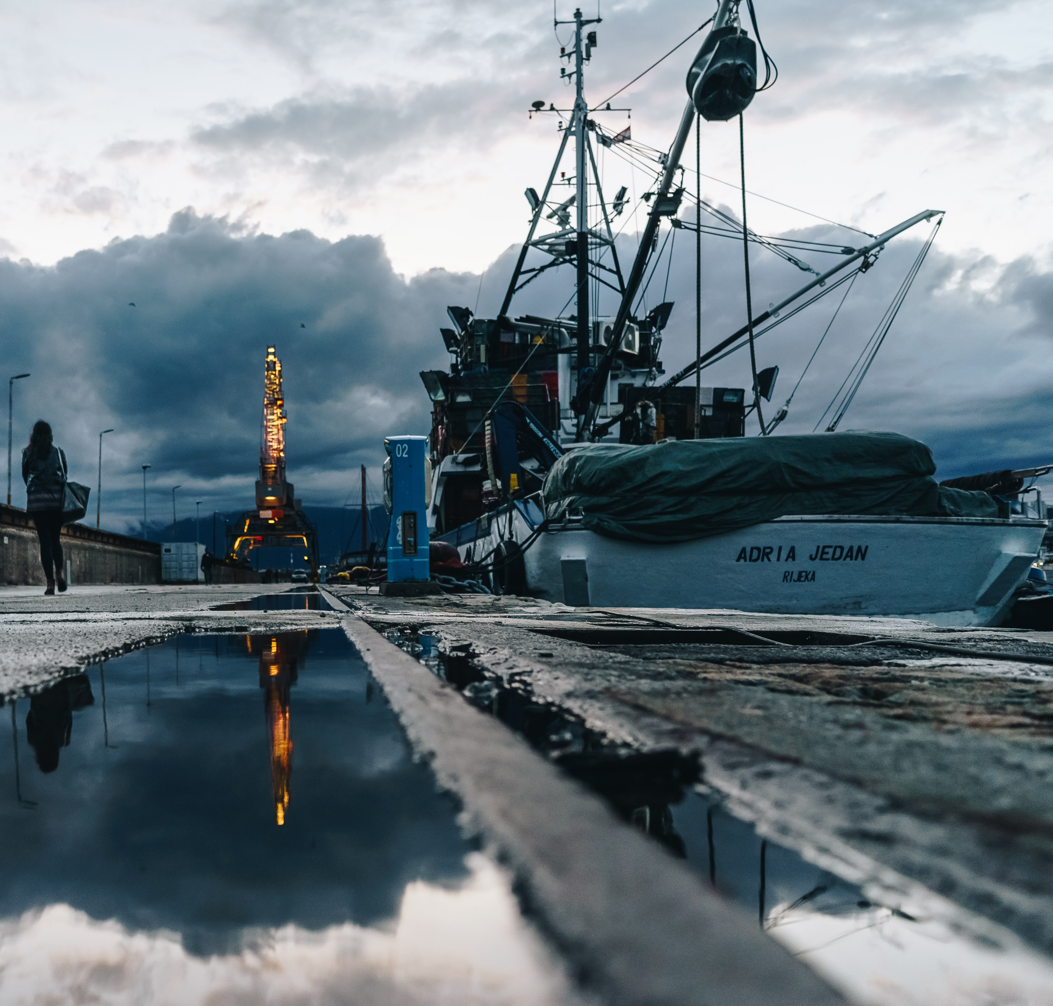 woman walking on pathway beside parked ship under white and blue cloudy skies