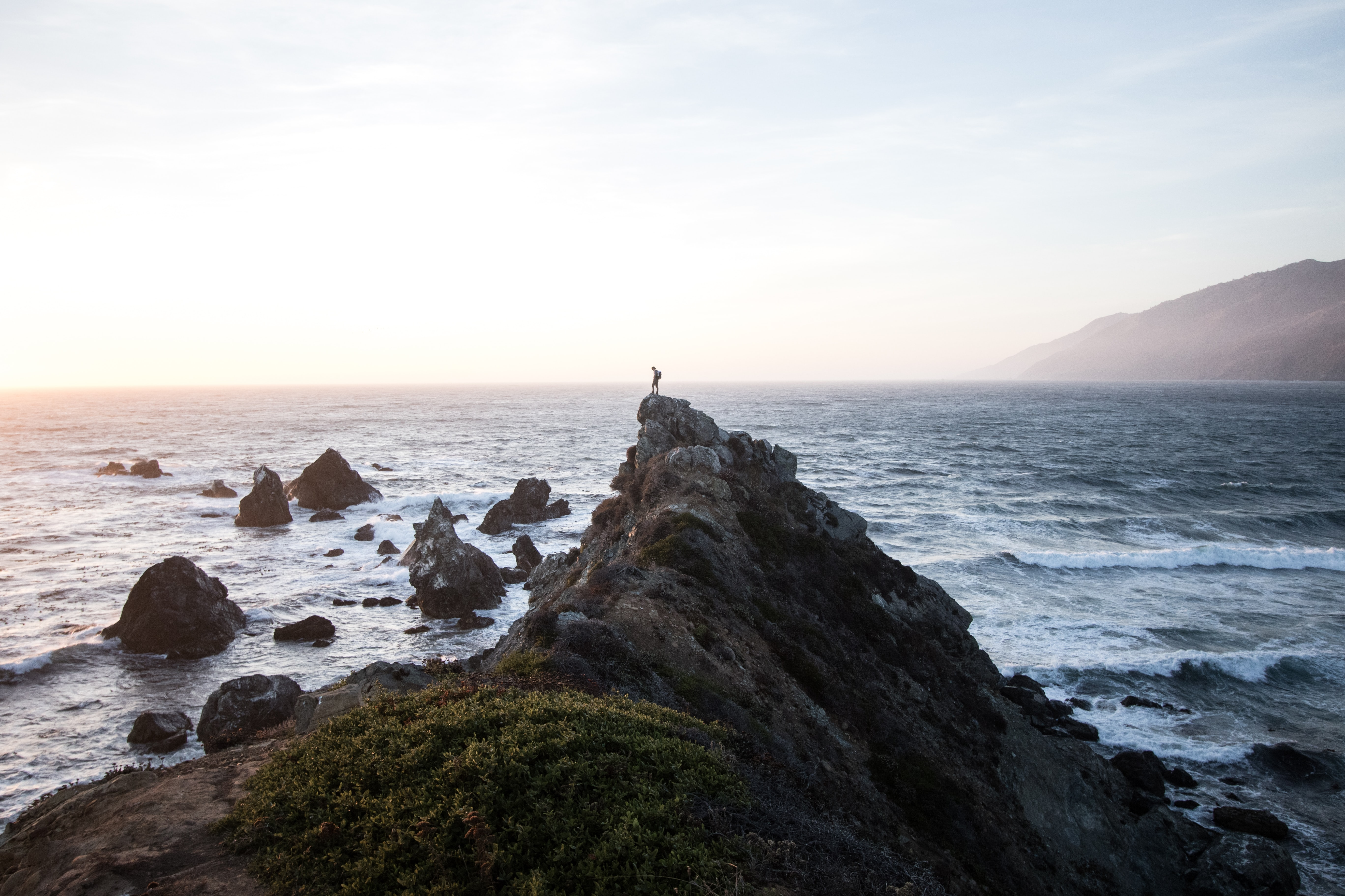 person standing on rock cliff near body of water