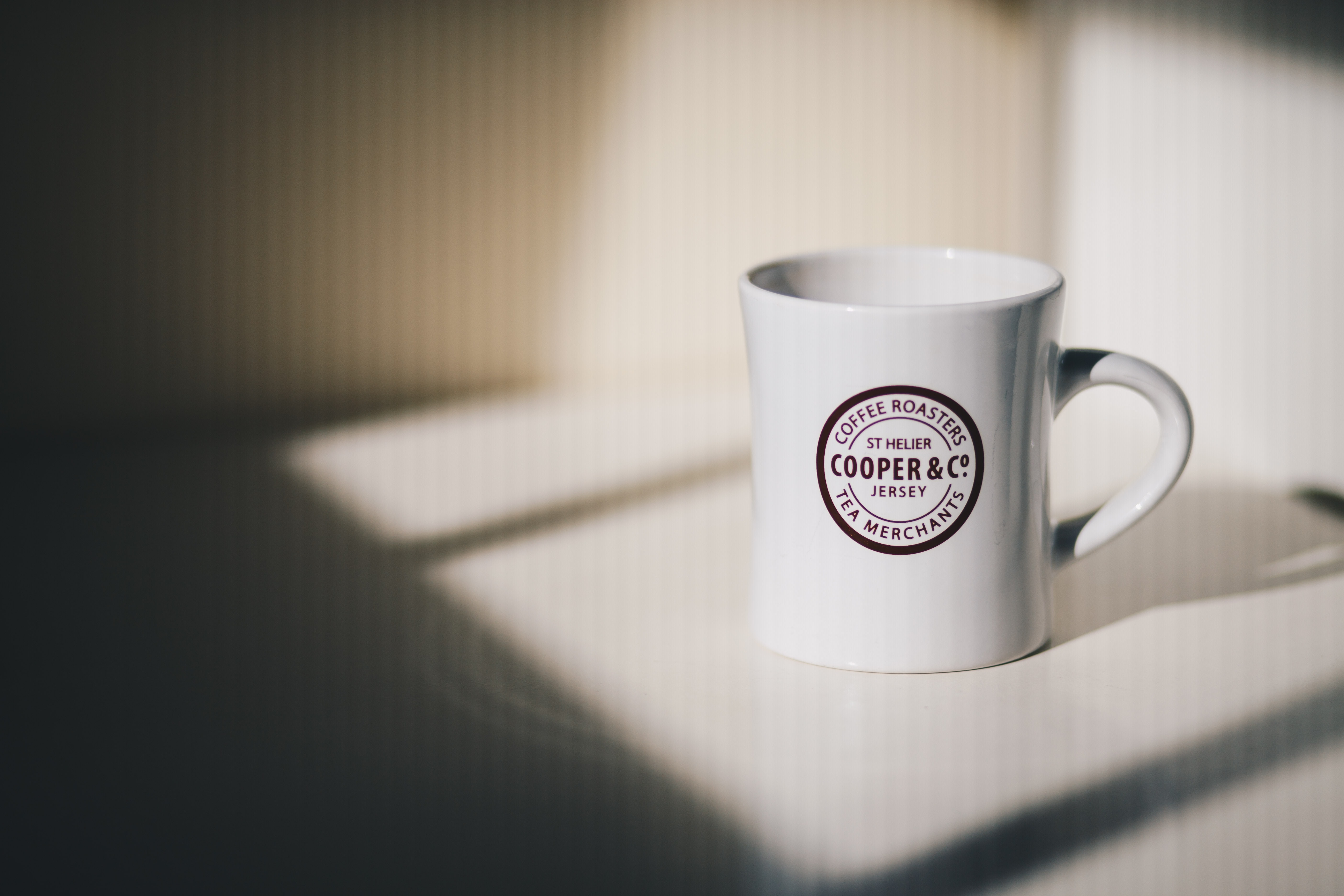 selective focus photo of white mug on white surrface