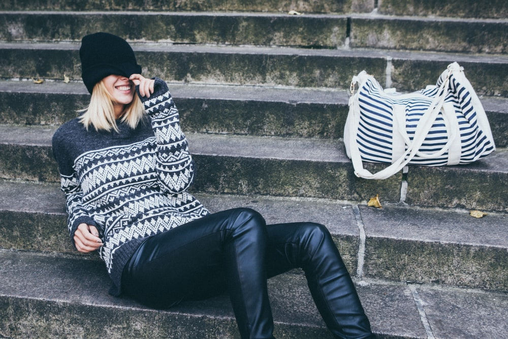 woman wearing gray and black tribal sweater and black pants sitting on gray concrete stair