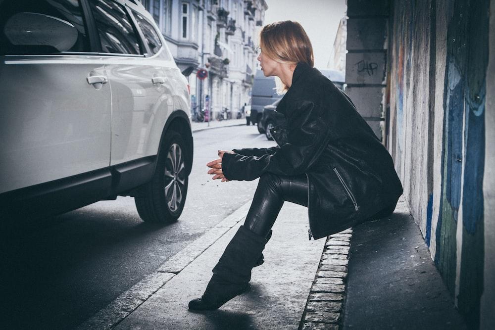 woman sitting on gray concrete sidewalk