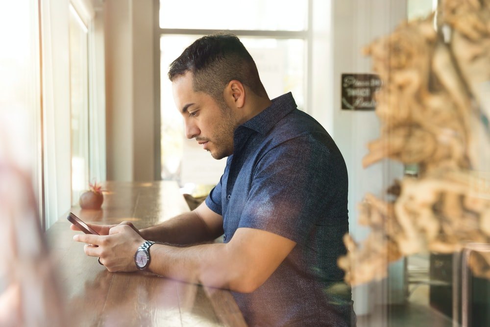 man in black button-up shirt holding smartphone