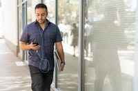 man in blue button-down shirt walking beside glass wall during dayhtime