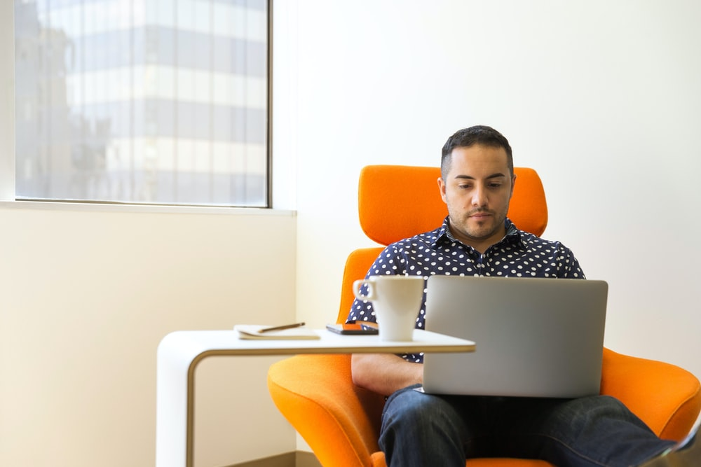 man wearing blue-and-white polka-dot collared shirt sitting on orange fabric sofa chair while using silver laptop beside white wooden desk with white ceramic mug
