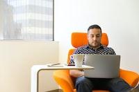 man wearing blue-and-white polka-dot collared shirt sitting on orange fabric sofa chair while using silver laptop beside white wooden desk with white ceramic mug