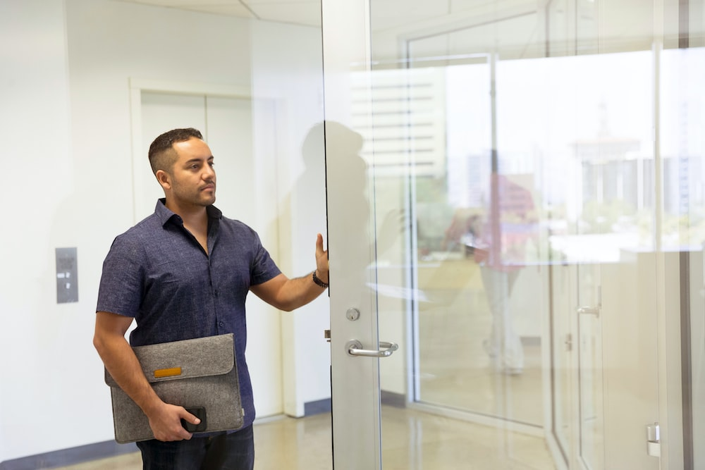 man in blue button-up collar top holding gray laptop bag and holding glass door