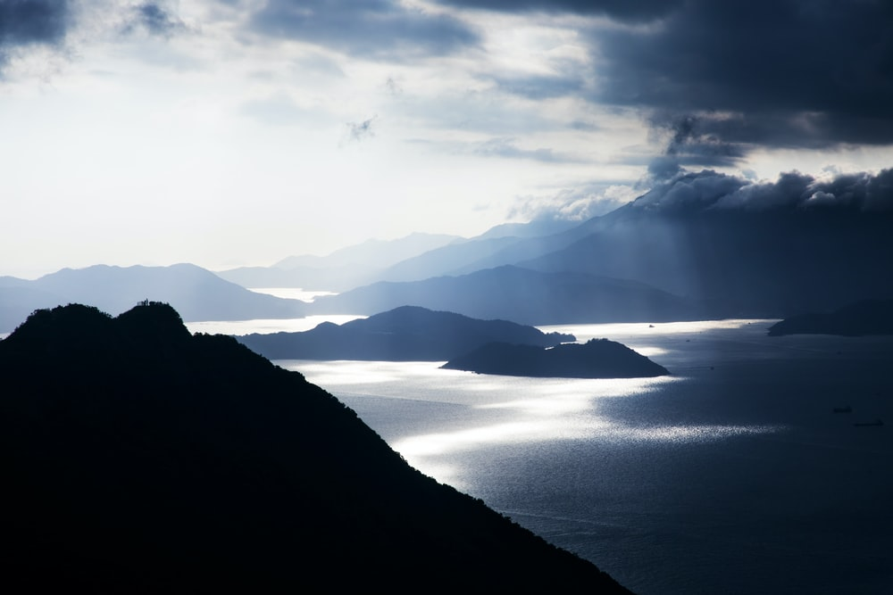 silhouette of mountains surrounded by body of water