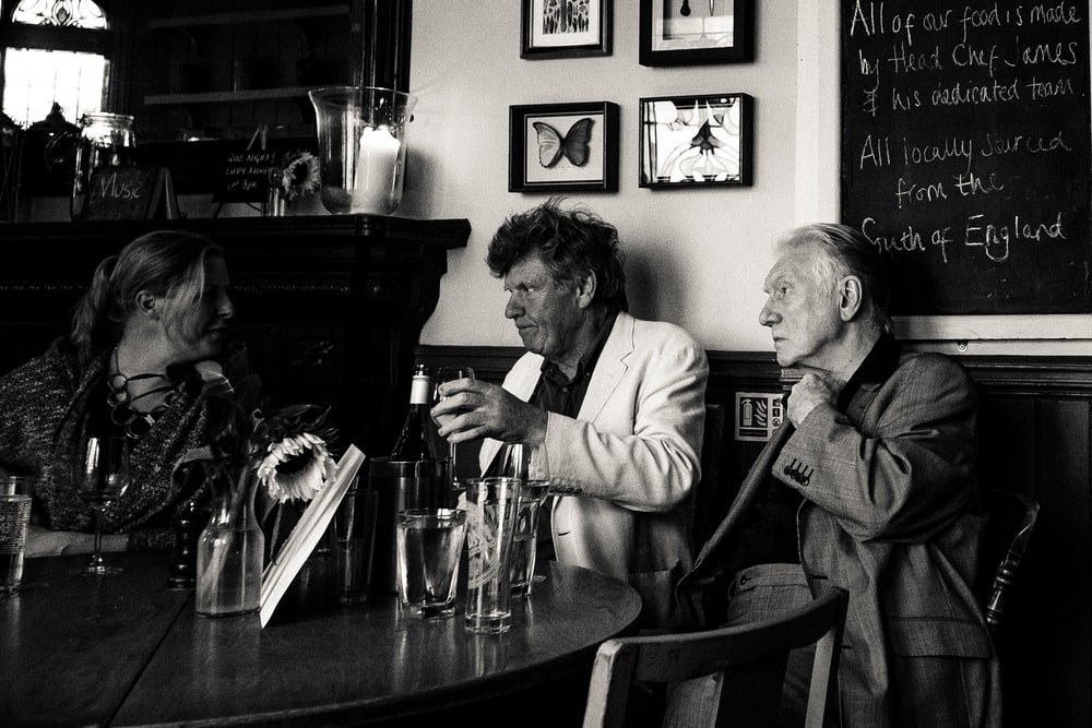 grayscale photo of three man sitting beside table