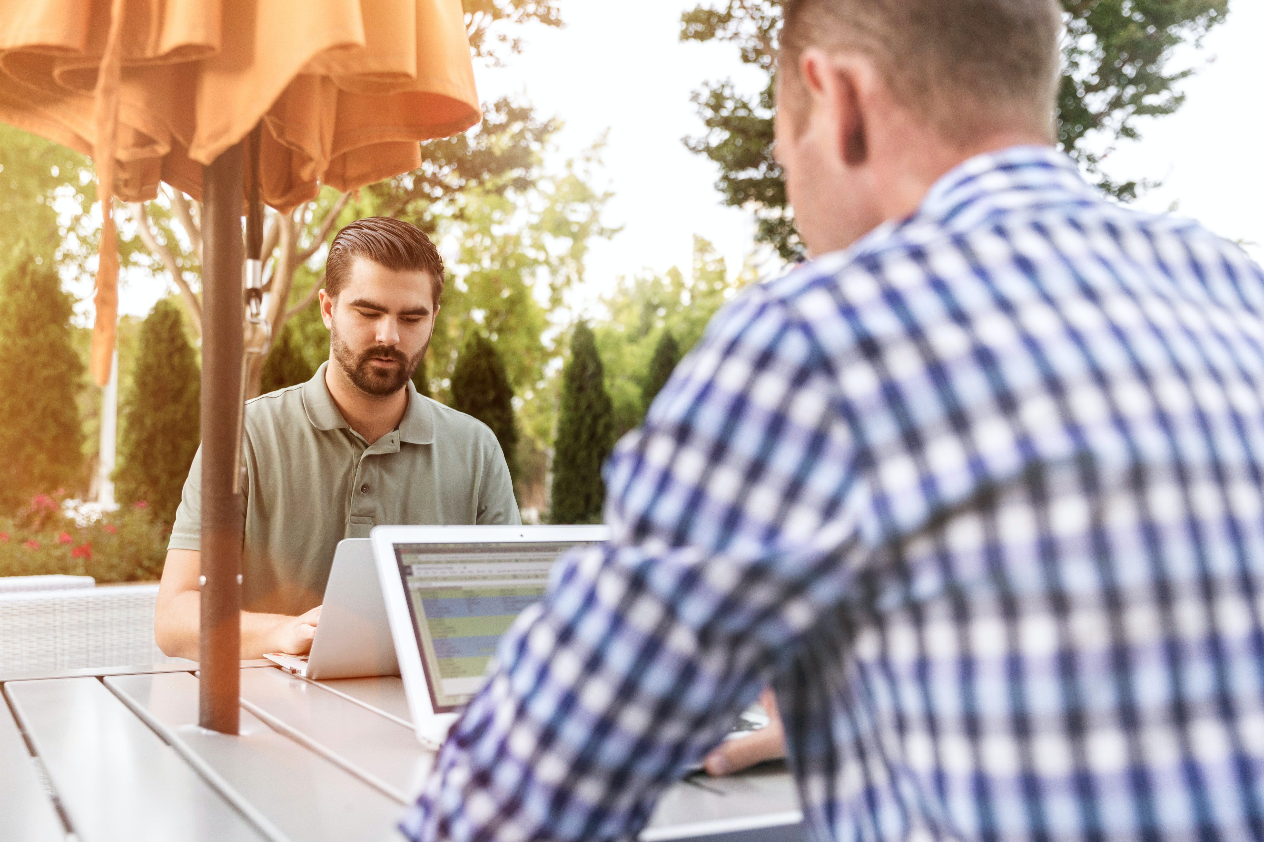 two person sitting on patio table using laptop computer
