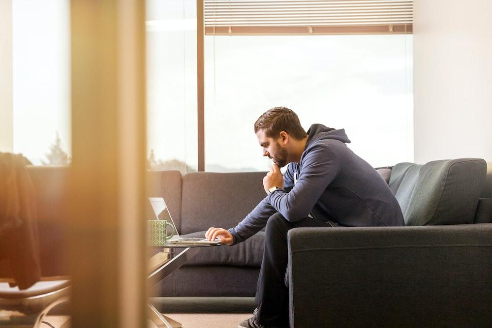 man sitting on sofa facing laptop computer
