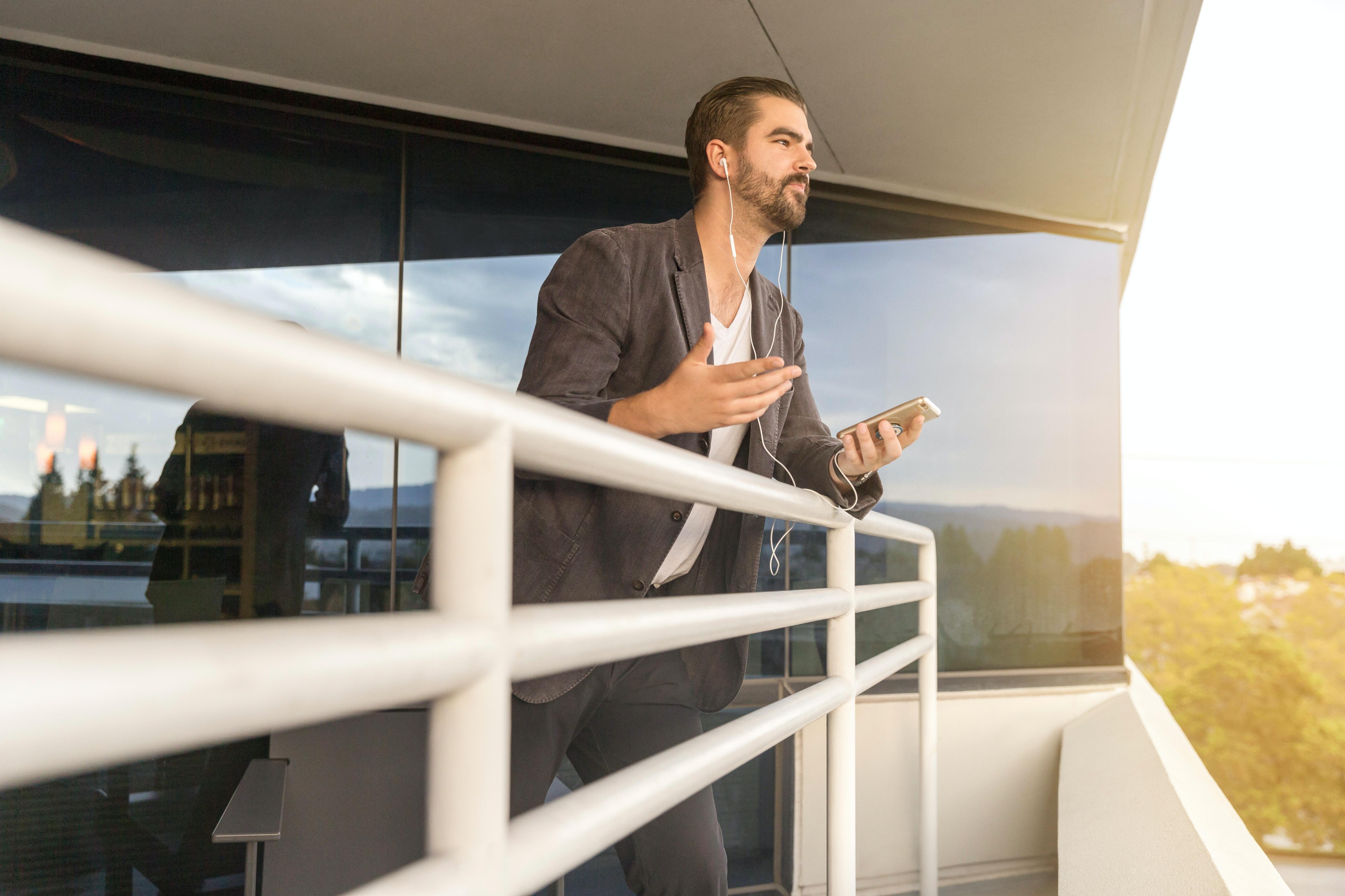 man leaning on white metal rail