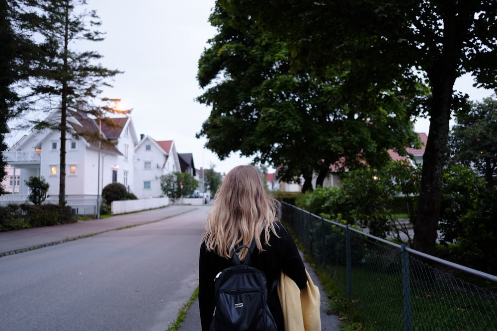 woman wearing black long-sleeved shirt and backpack walking on gray concrete road between green trees near white concrete house during daytime