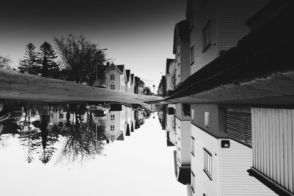 grayscale photo of house near street reflects on body of water