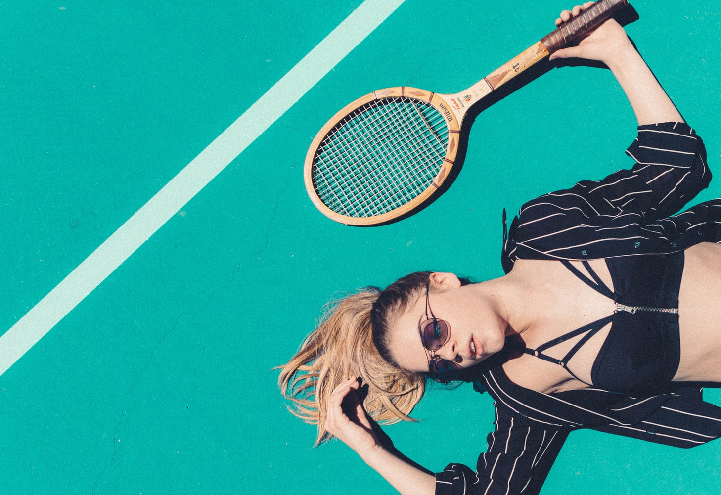 Woman lying on the tennis field is wearing a tennis rocket and wearing the best sunglasses for tennis