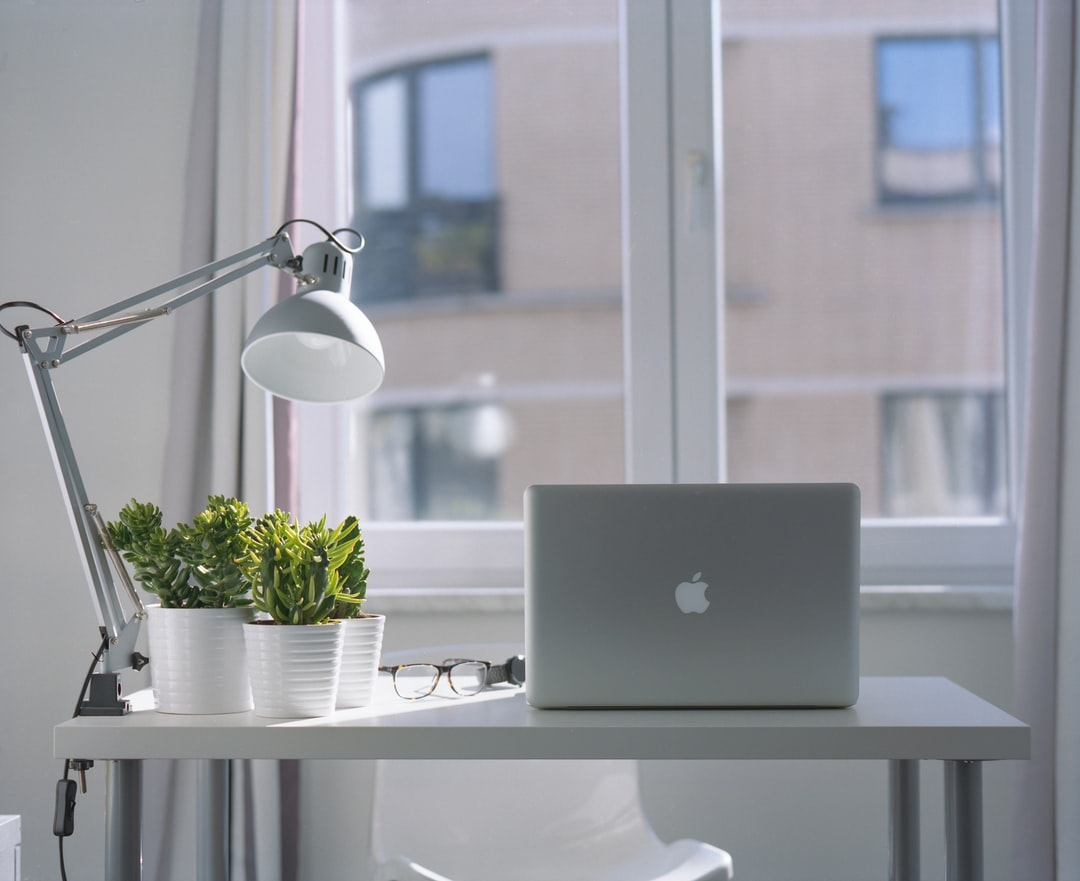 A beautyshot of my old 2012 Macbook Pro on a cheap ikea desk, cheap ikea lamp and cheap ikea plants and pots, in my college apartement.