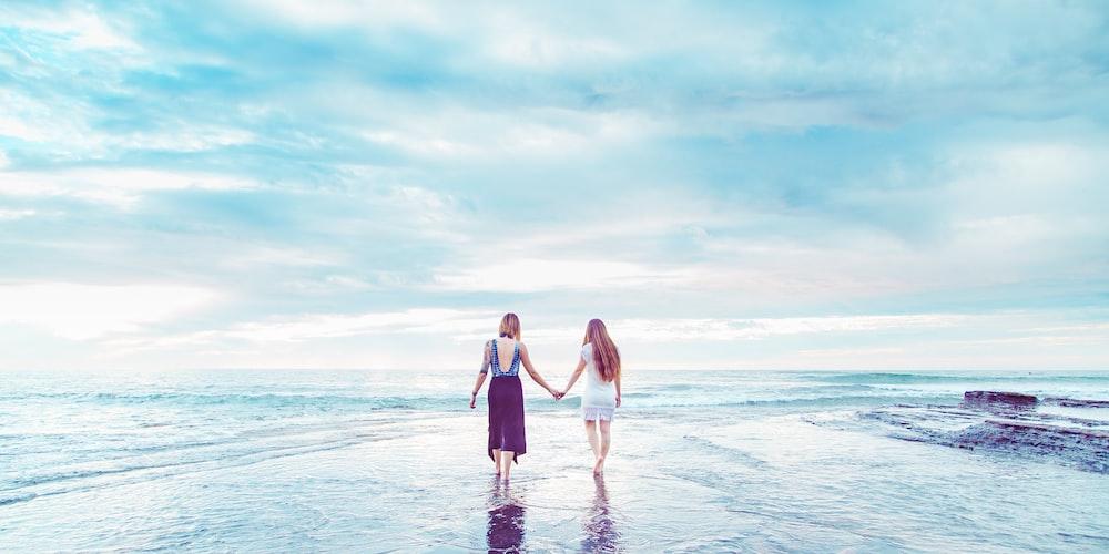 two women walking on shoreline holding hands