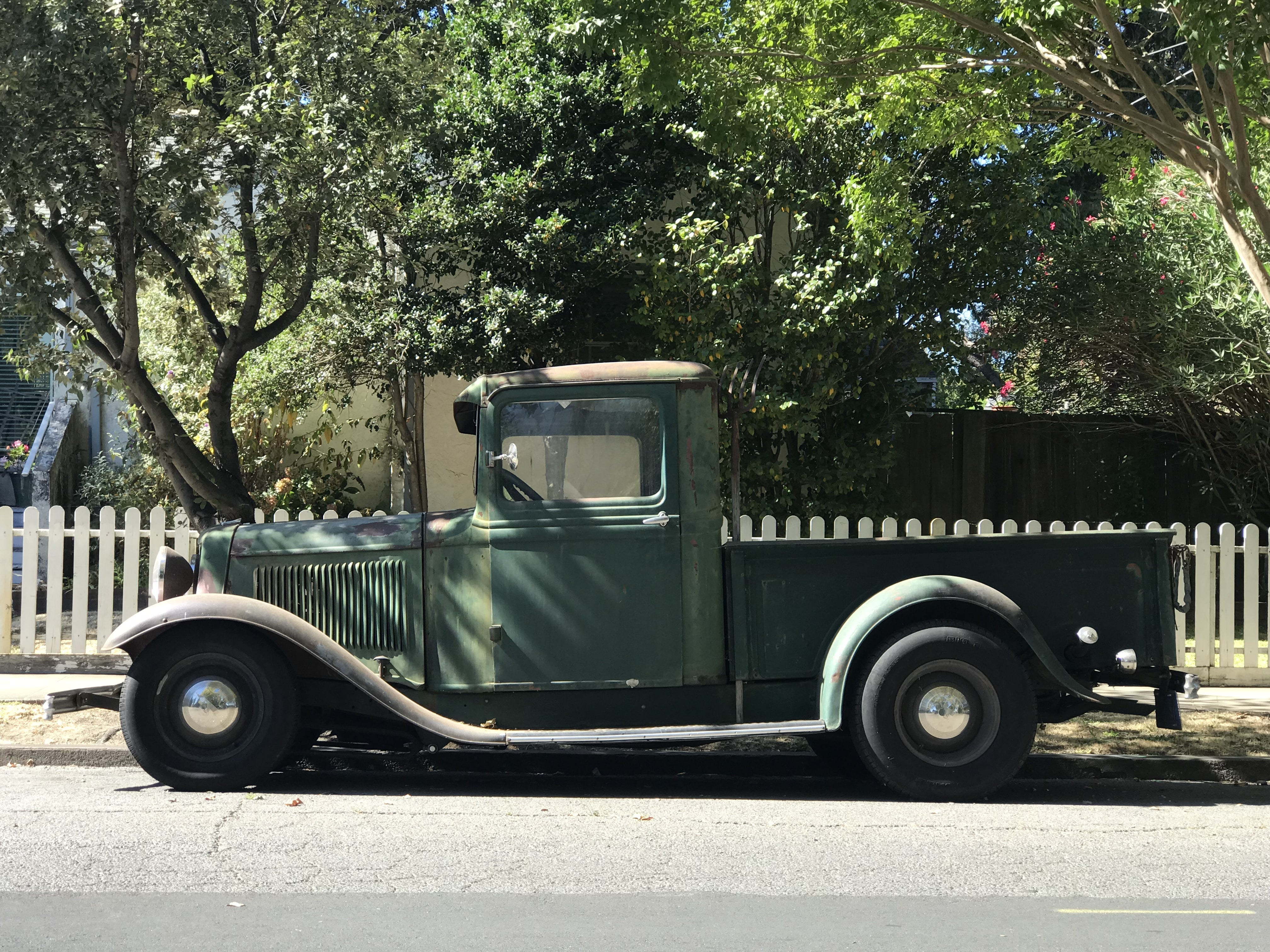 vintage green vehicle near white fence during daytime