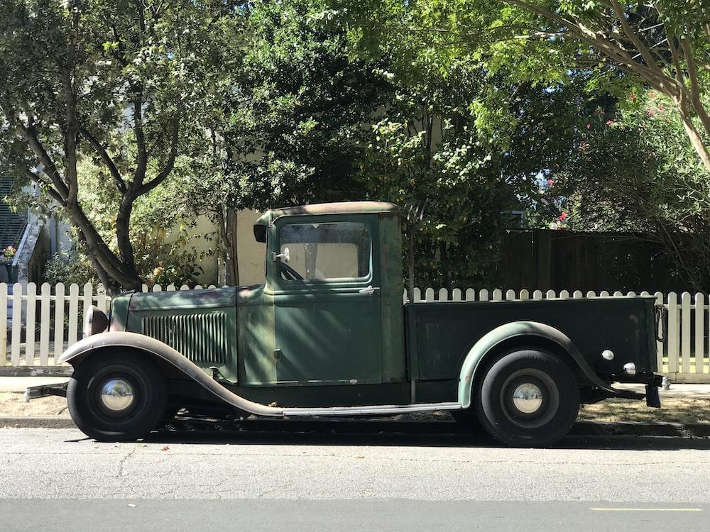 vintage green vehicle near white fence during daytime