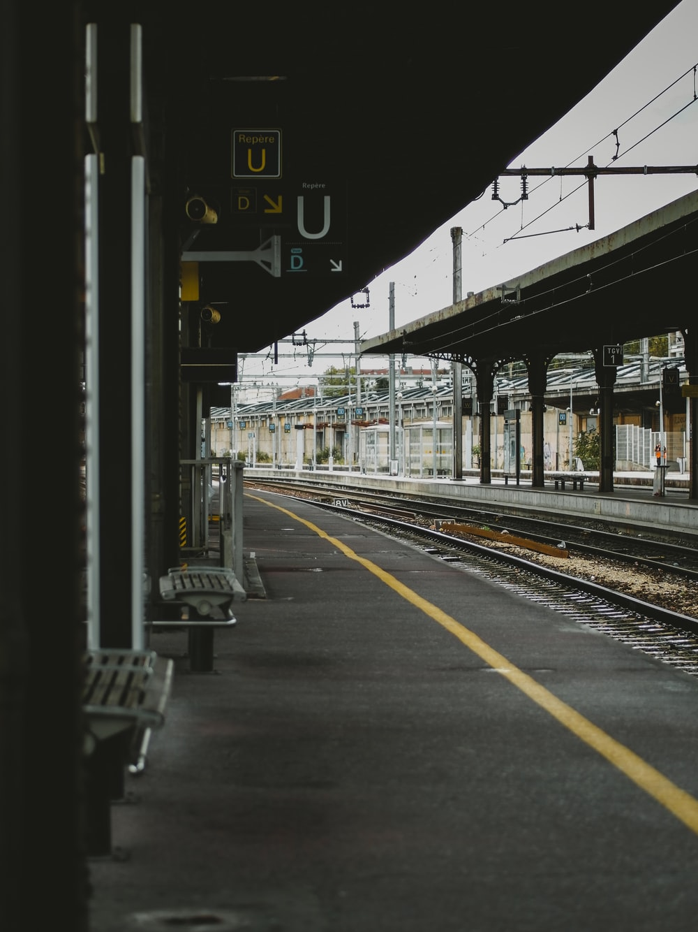 empty benches on train station beside railway at daytime