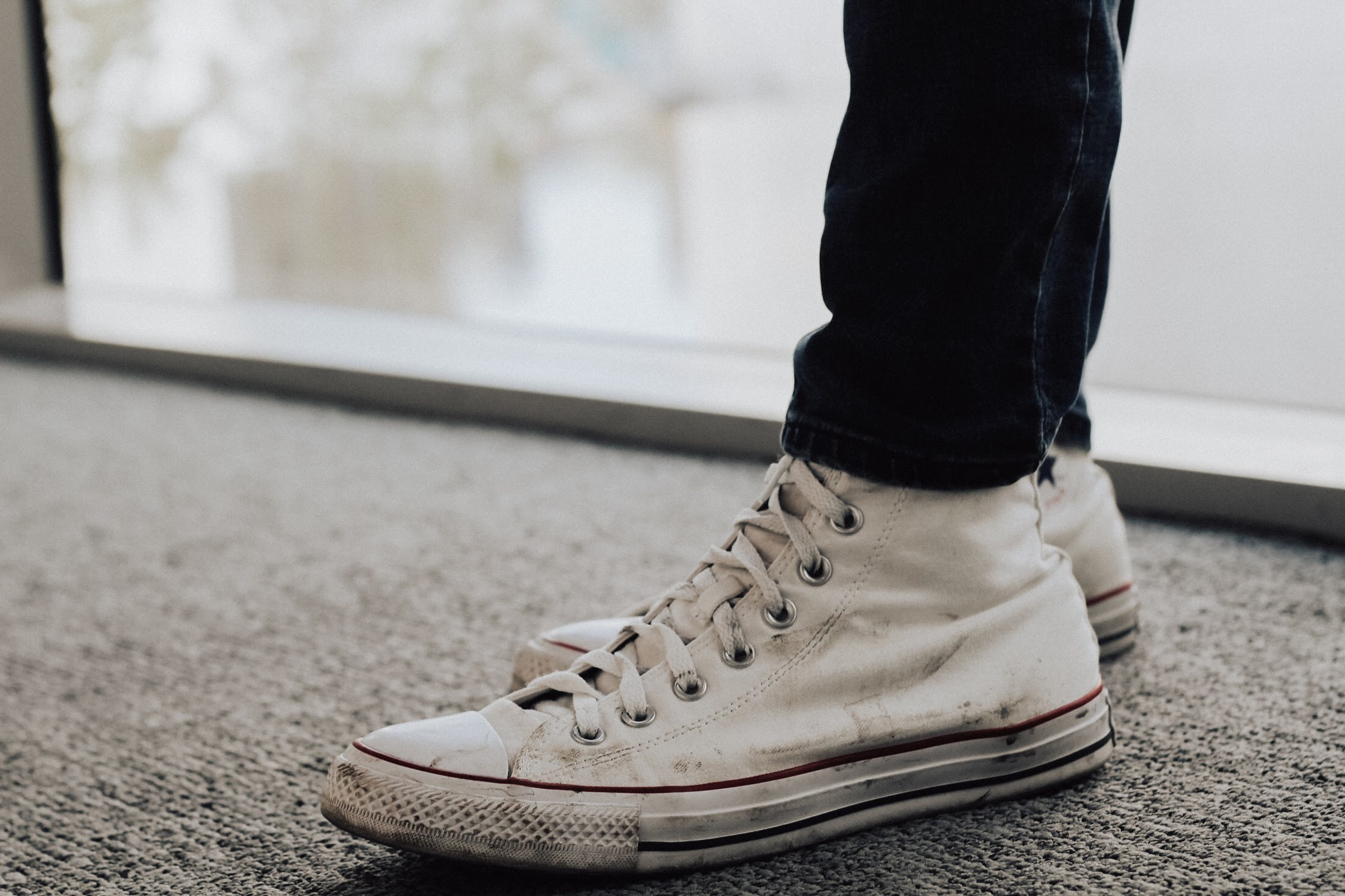 person wearing white high-top sneaker standing on gray carpet close-up photo
