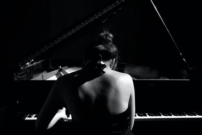 selective focus photography of woman playing grand piano