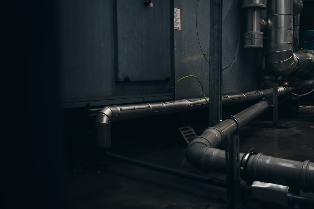 gray pipes mounted on concrete wall arrangement