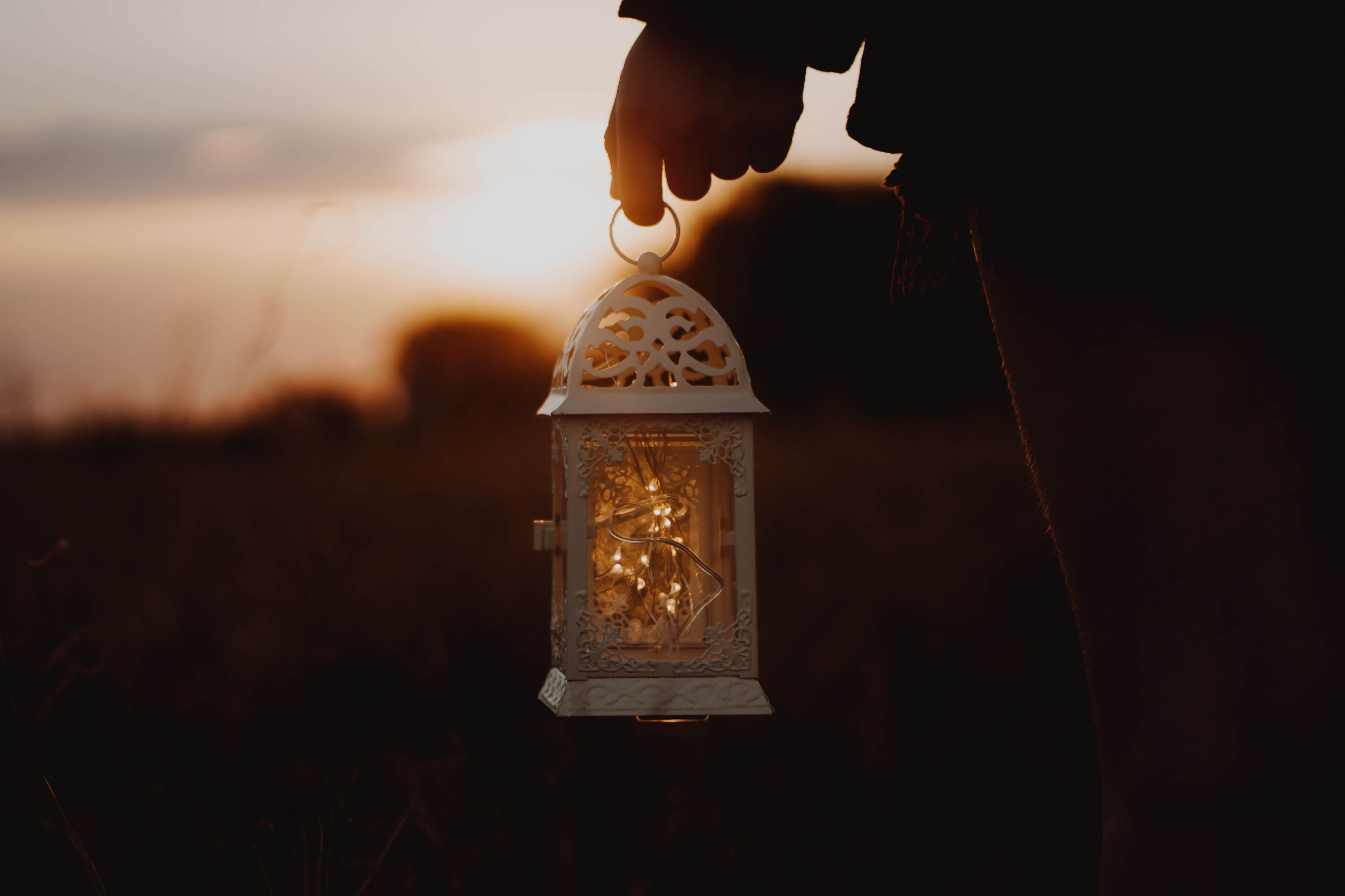 person holding white metal framed clear glass lantern during golden hour