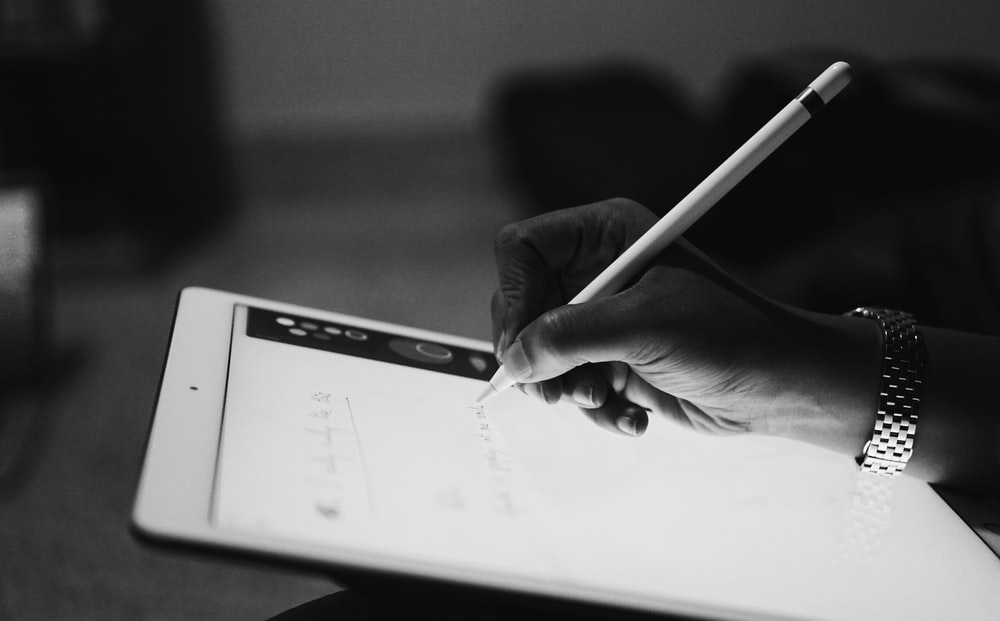 person typing by Apple Pencil on iPad in a room