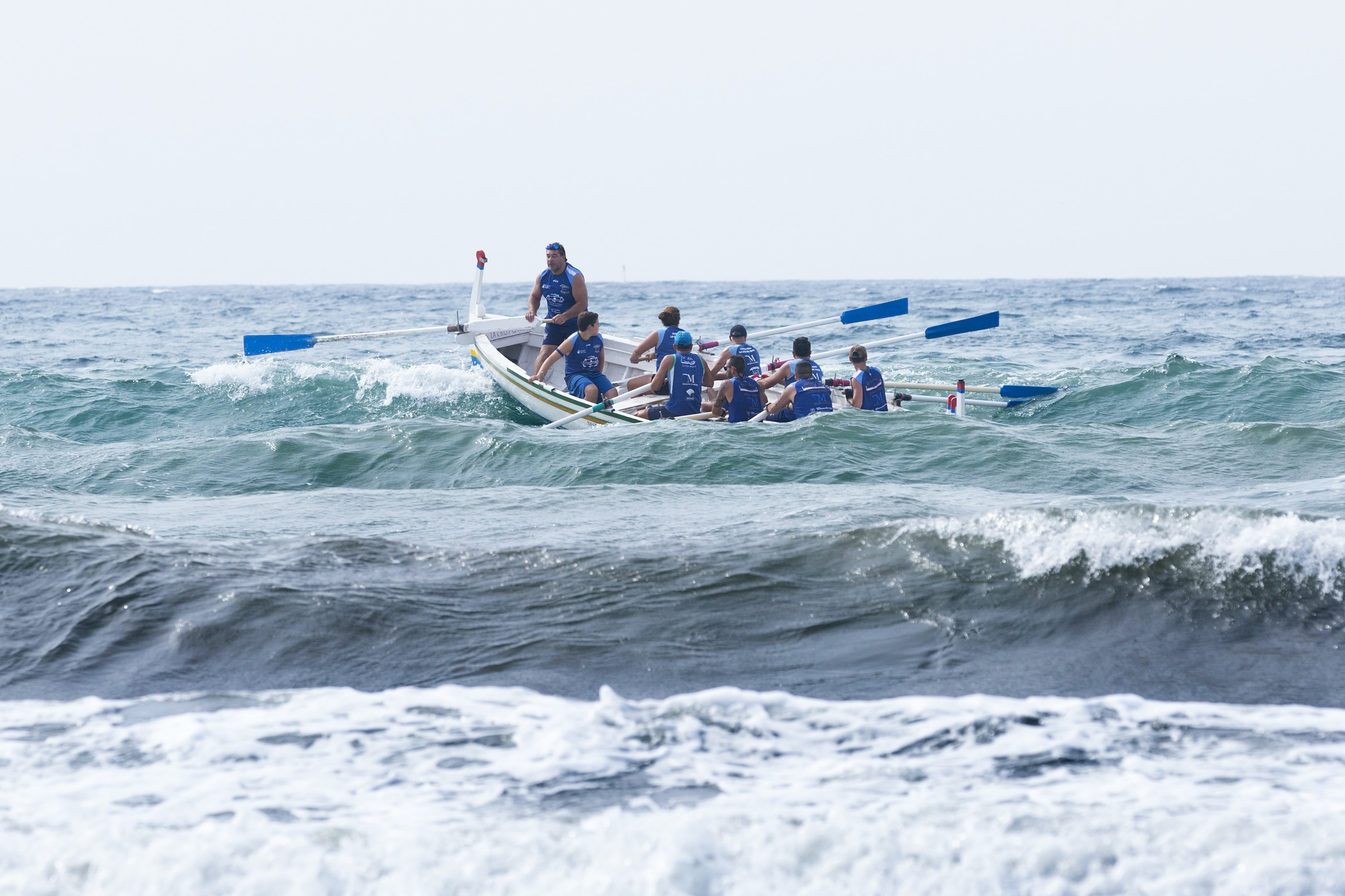 group of men boating on violent waves during daytime