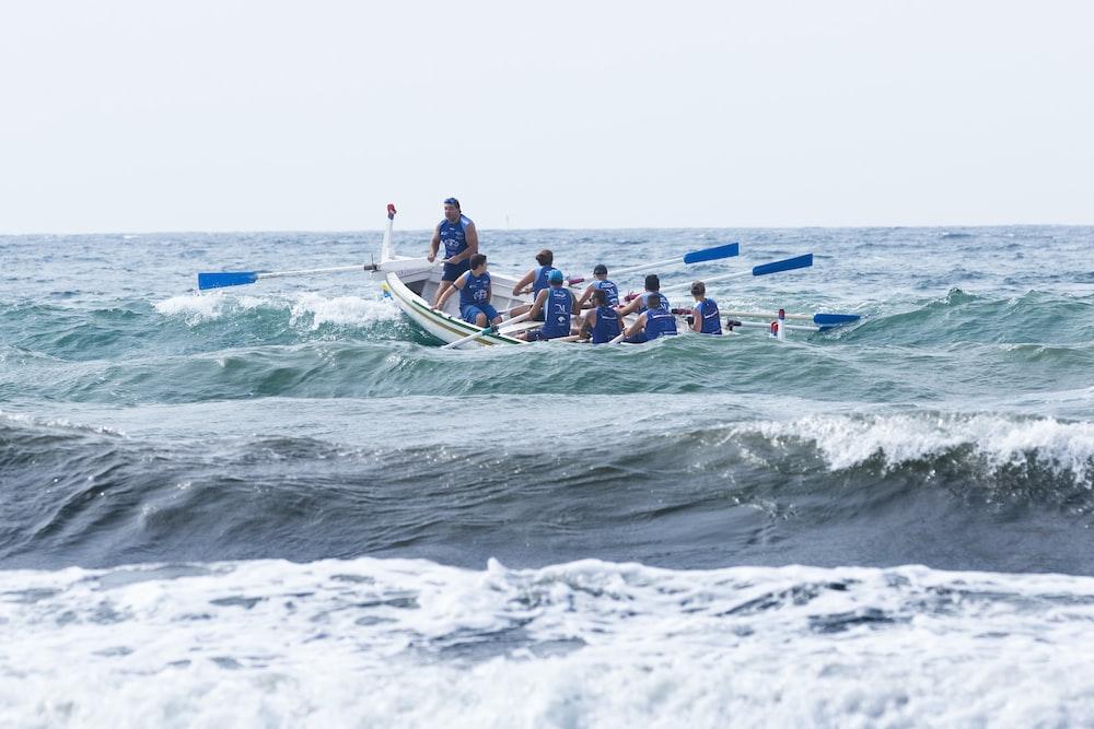 group of men boating on violent waves during daytime