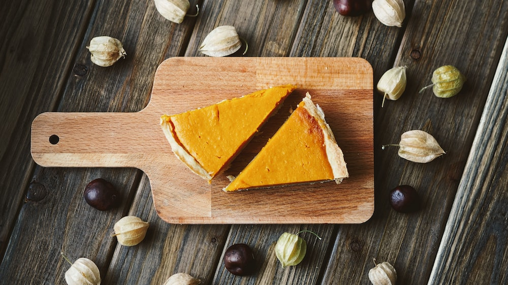 two sliced pies on brown wooden chopping board