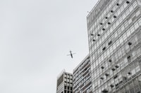 low-angle photography of airliner and high-rise buildings