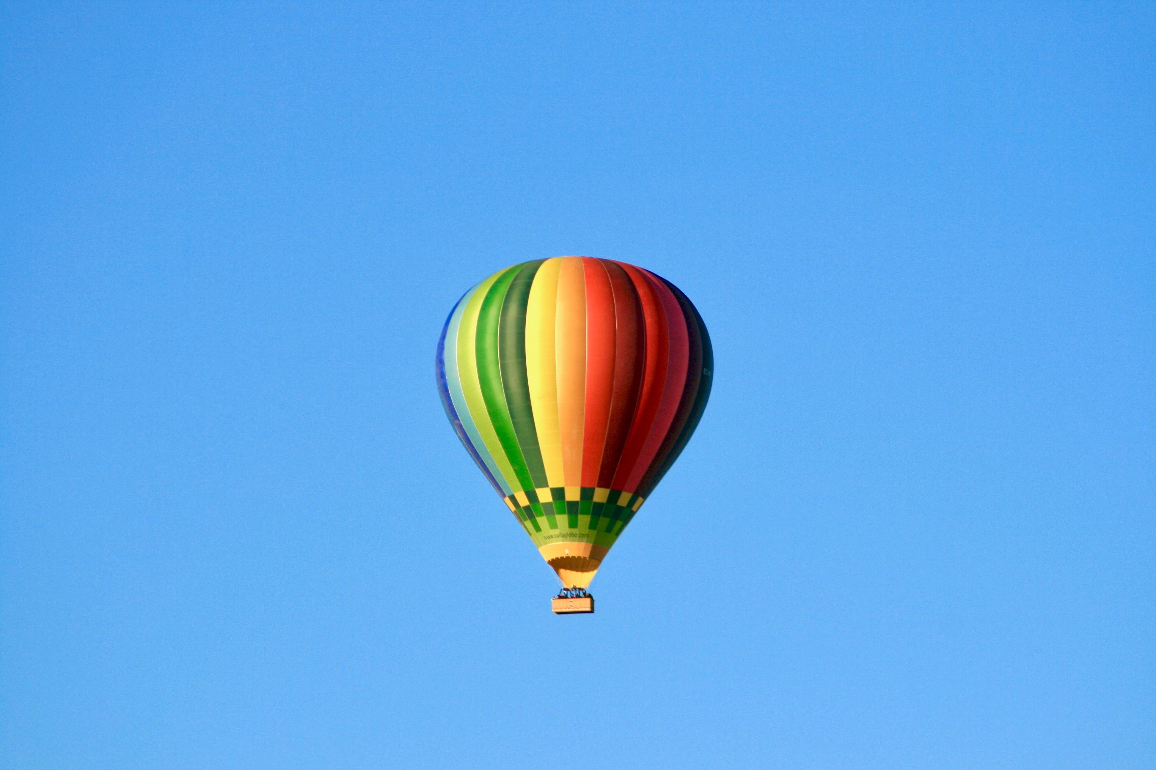 low angle photo of multicolored hot air balloon flying under blue skty