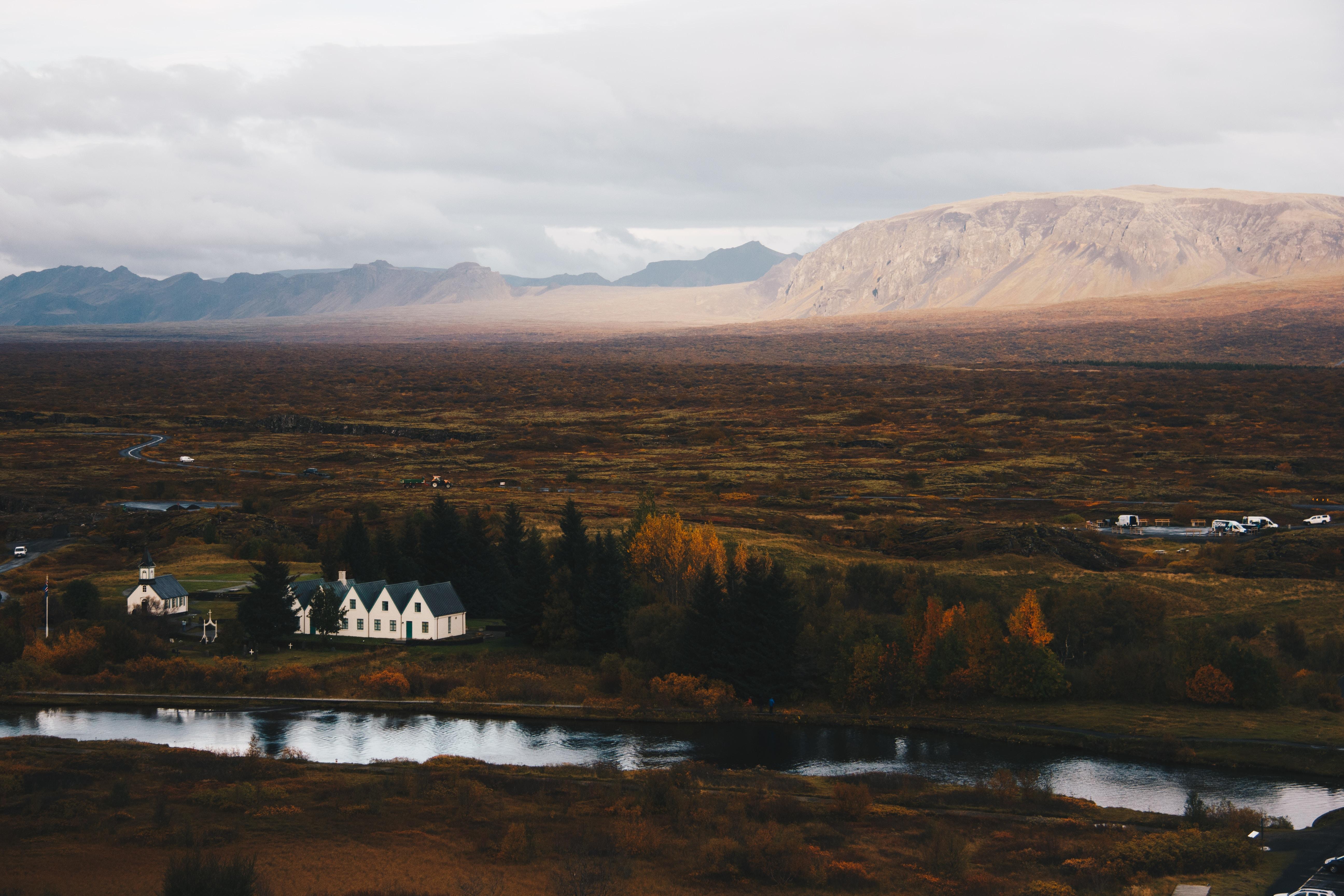 house near lake under white sky during daytime