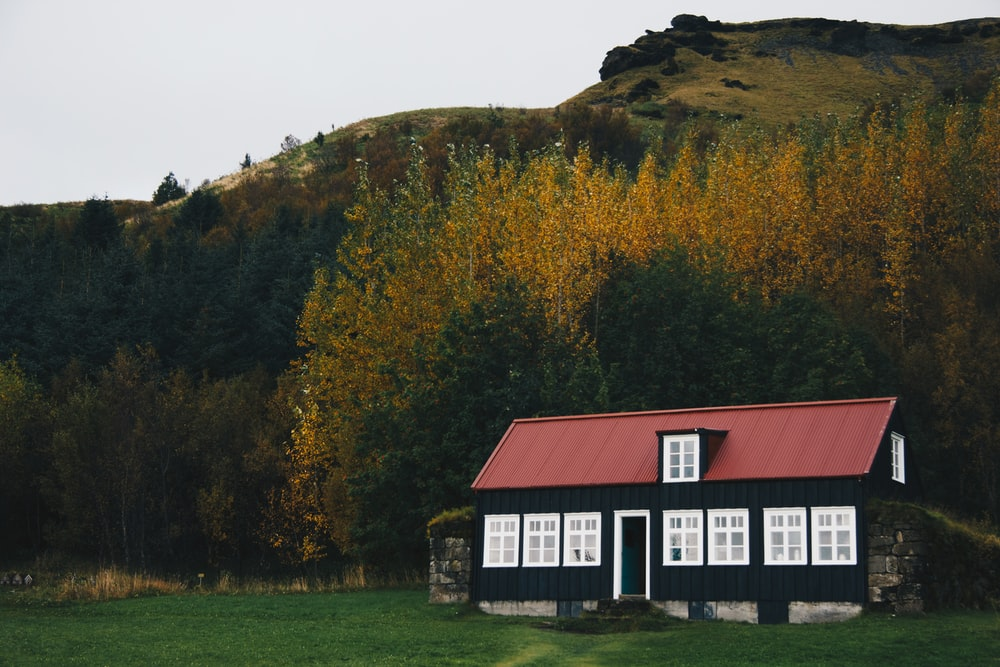 black and red wooden house near mountain