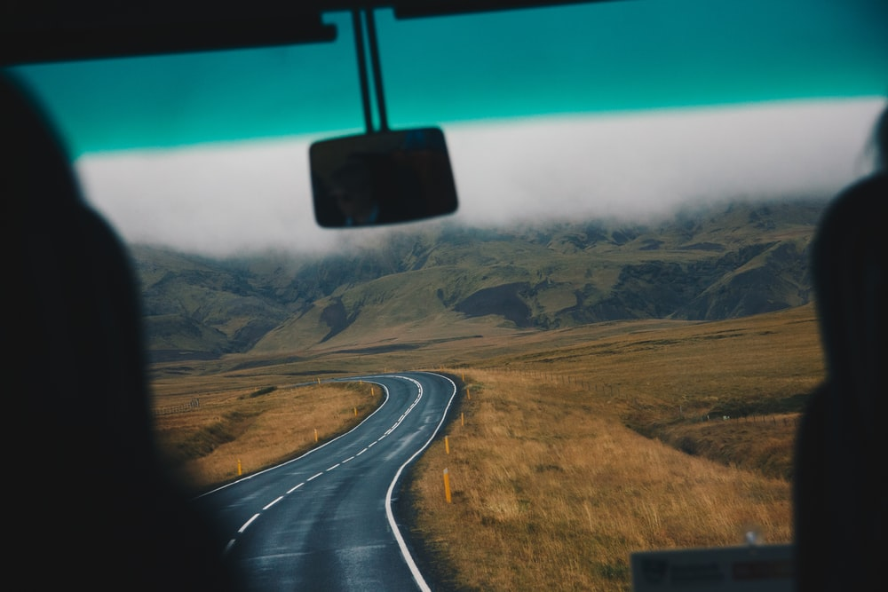 concrete road leading to green mountain