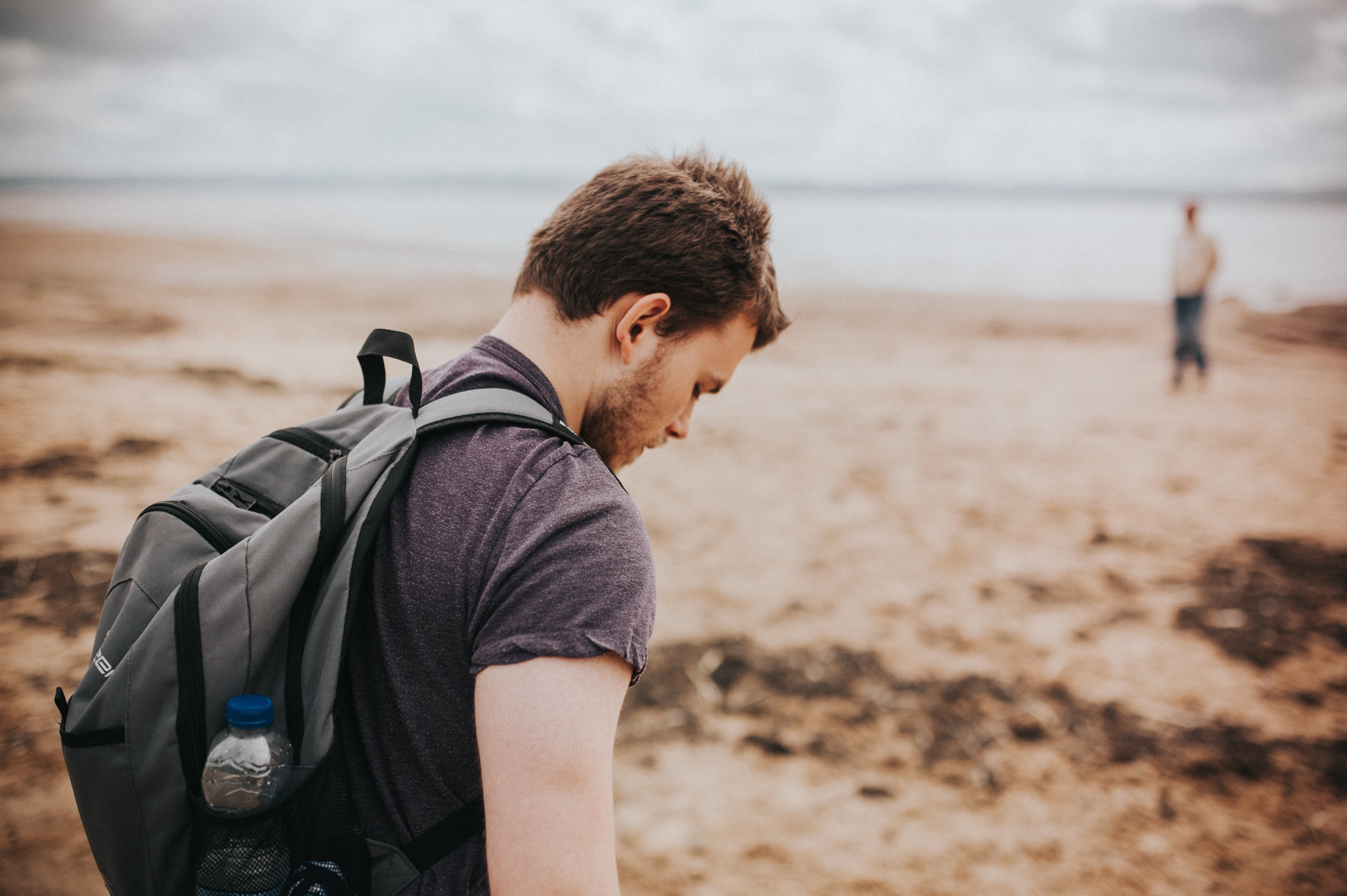 man in gray shirt and backpack beside beach shore during daytime