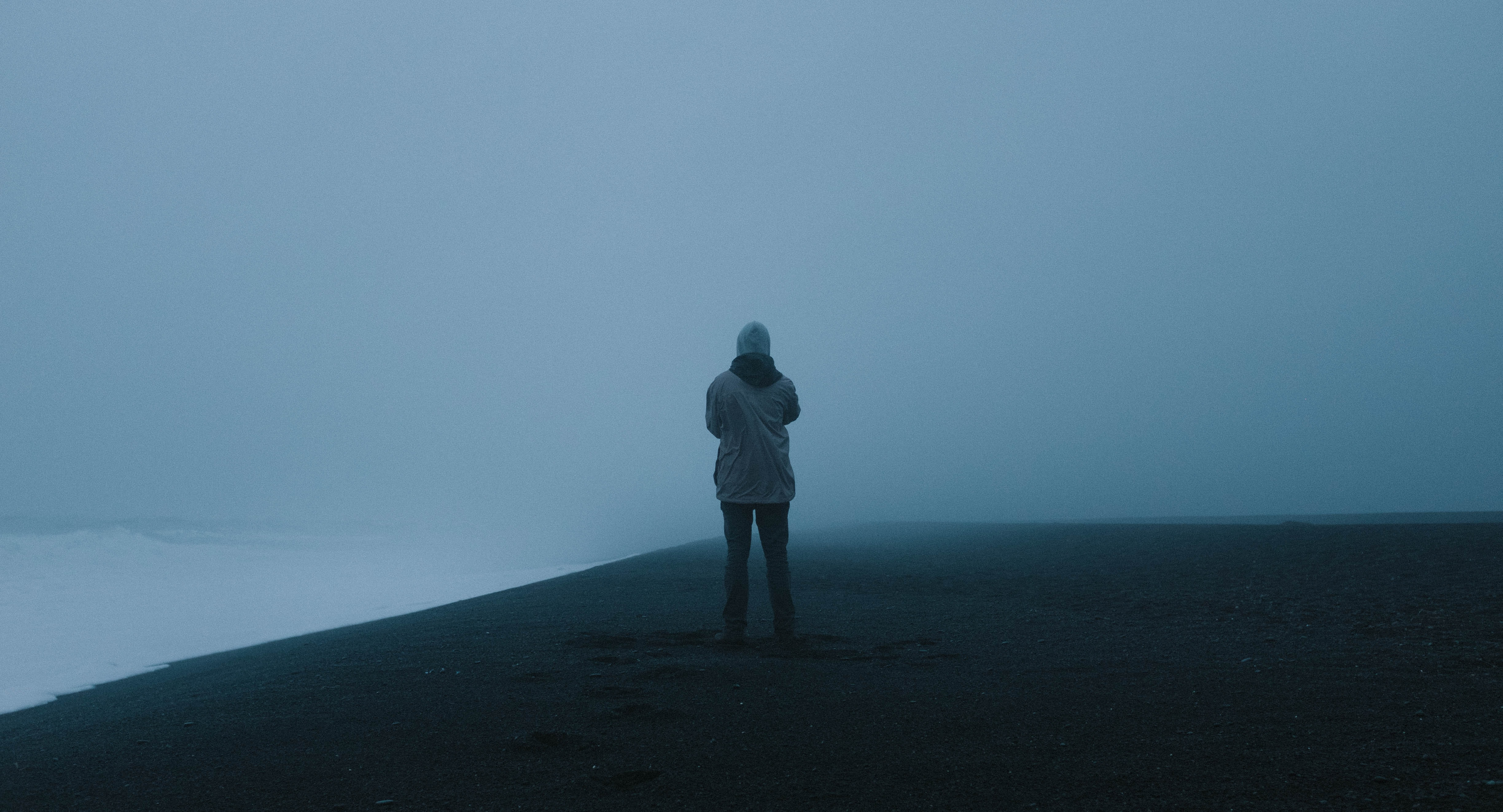 person standing on hill covered by fog