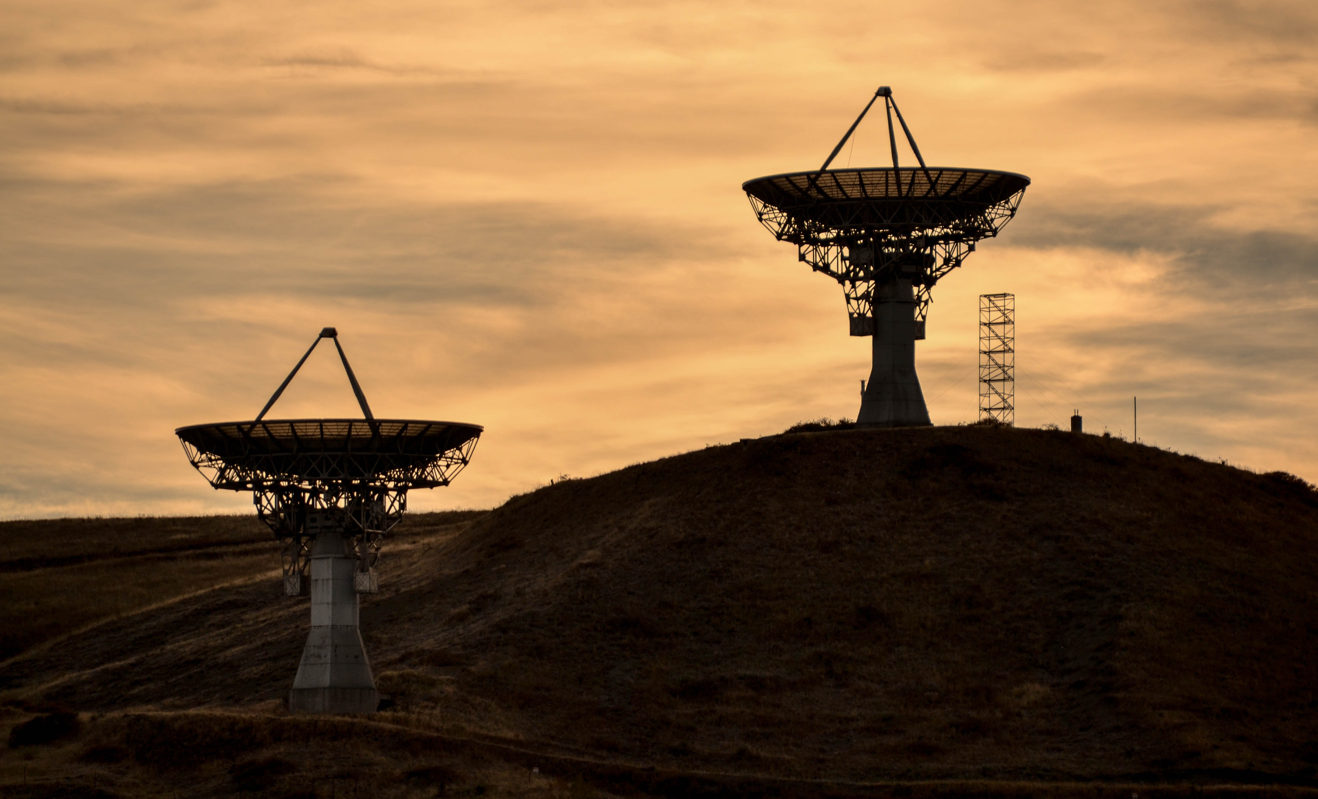 two gray satellites at sunset