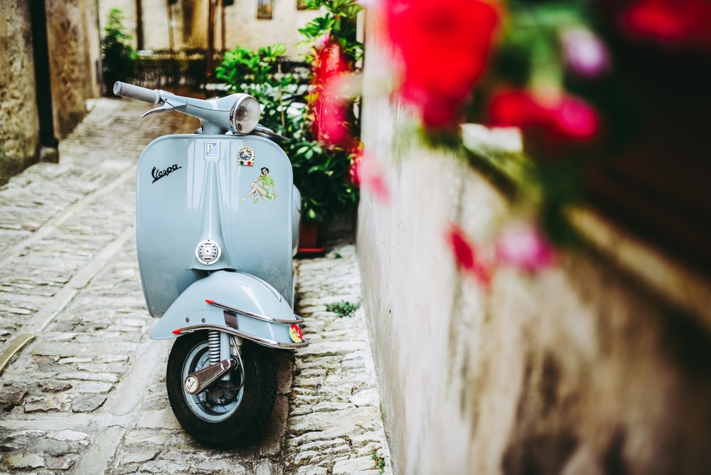 selective focus photo of blue motor scooter beside concrete wall