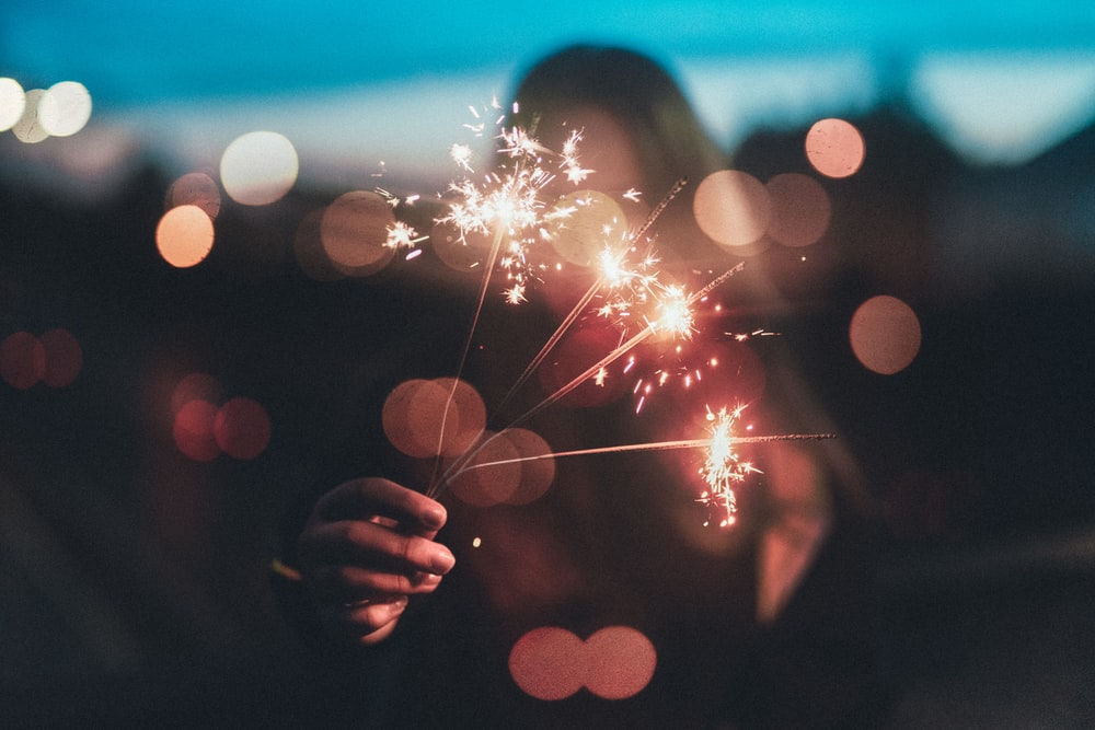 woman holding firework sticks in shallow photography