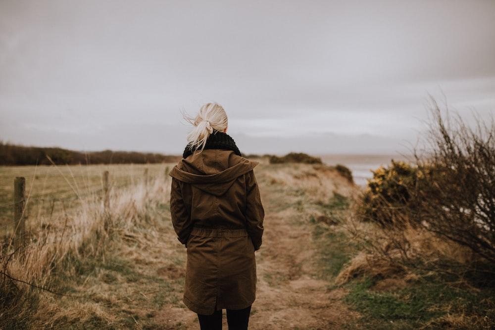 woman in brown coat walking on brown grass